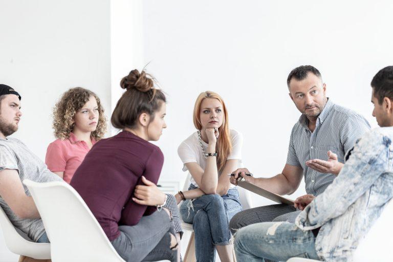 Terapia en centro de desintoxicación hablando sobre los problemas en la recuperación de adicciones